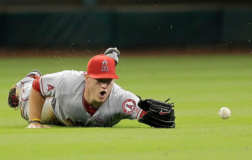 . HOUSTON, TX - SEPTEMBER 14:  Mike Trout #27 of the Los Angeles Angels of Anaheim dives but can\'t make the catch on a shallow fly ball hit by Matt Dominguez #30 of the Houston Astros in the sixth inning at Minute Maid Park on September 14, 2013 in Houston, Texas.  (Photo by Bob Levey/Getty Images)