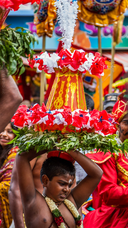 A group of several young men spin tall, colorful tops above their heads throughout the procession.
