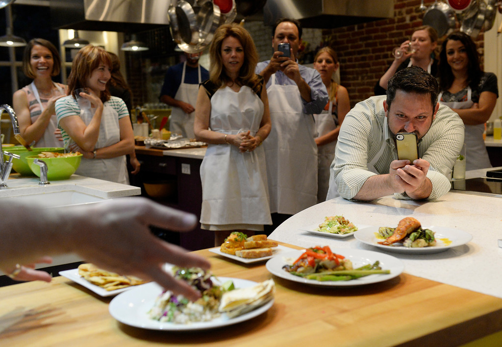 . DENVER, CO - JUNE 6: Contestants take photos and listen to descriptions of the final creations as  Stir Cooking School at 3215 Zuni Street in Denver, hosted an Iron Chef styled cooking event  on Friday, June 6, 2014.  The evening pitted three tables competing against one another.  (Denver Post Photo by Cyrus McCrimmon)