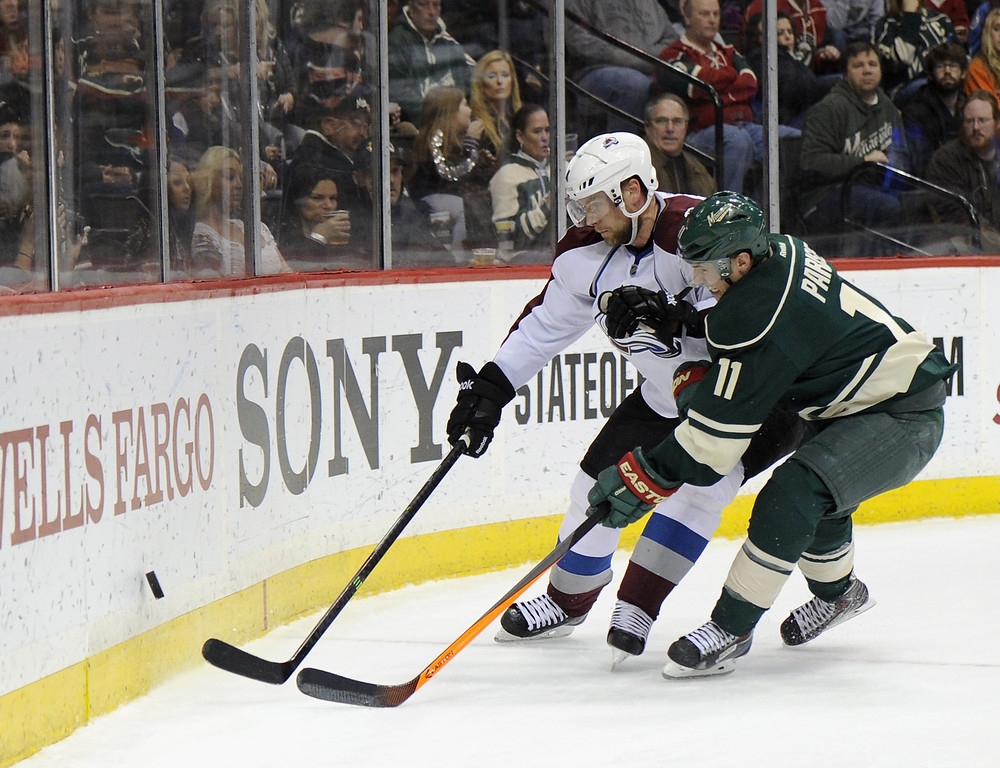 . Jan Hejda #8 of the Colorado Avalanche and Zach Parise #11 of the Minnesota Wild skate after the puck during the second period of the game on November 29, 2013 at Xcel Energy Center in St Paul, Minnesota. (Photo by Hannah Foslien/Getty Images)