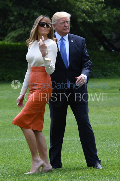 President Donald Trump and First Lady Melania Trump walk to Marine One as they leave for a nine day overseas trip.