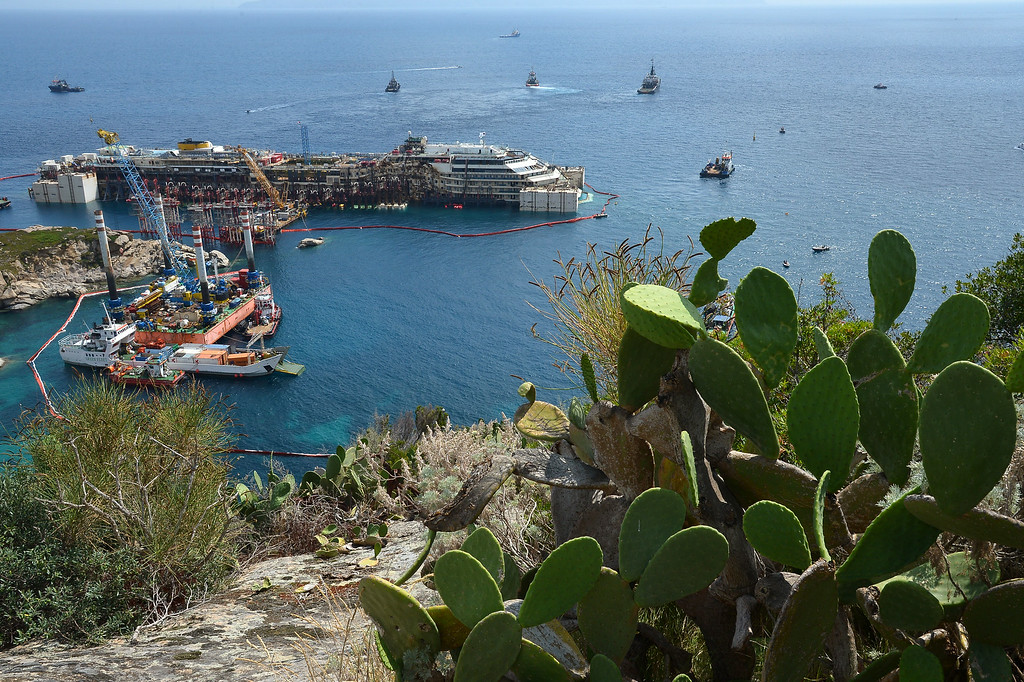 . A general view shows the wreck of the Costa Concordia cruise ship during an operation to refloat the liner on July 14, 2014 off the Giglio Island. Over two and a half years after it crashed off the island of Giglio in a nighttime disaster which left 32 people dead, the plan is to raise and tow away the 114,500-tonne vessel in an unprecedented and delicate operation for its final journey to the shipyard where it was built in the port of Genoa.           (VINCENZO PINTO/AFP/Getty Images)