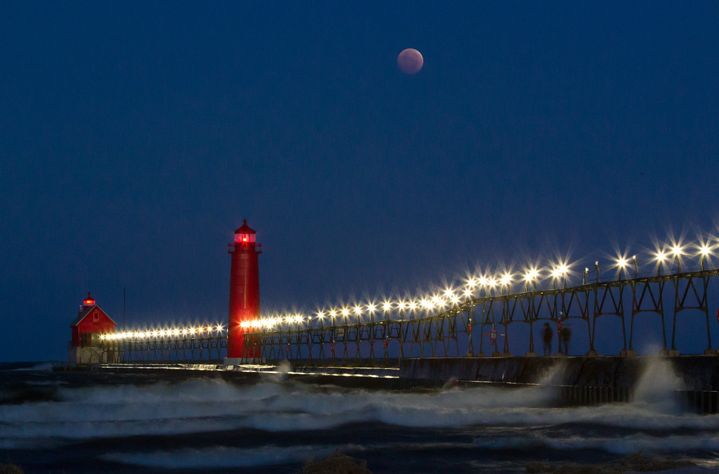 . A lunar eclipse appears above Grand Haven State Park Wednesday, Oct. 8, 2014 in Grand Rapids, Mich. The moon appears orange or red as it reflects the suns color in the Earth\'s atmosphere. This is known as the blood moon. (AP Photo/The Grand Rapids Press, Cory Morse)