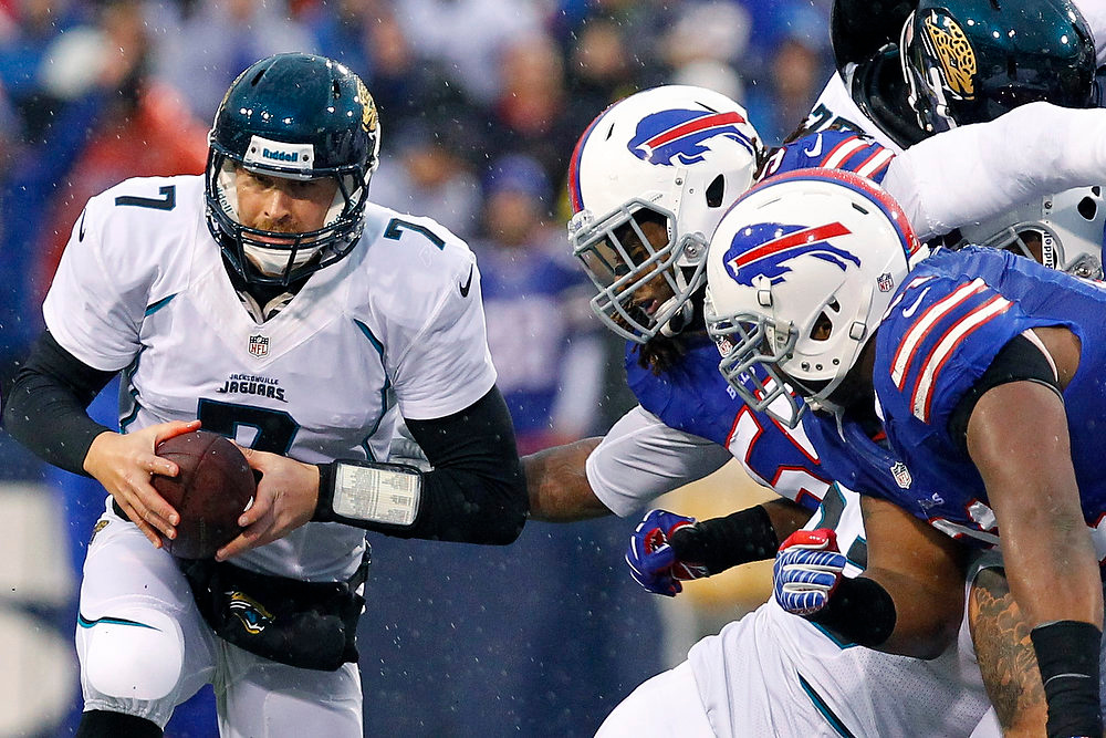 . Jacksonville Jaguars\' Chad Henne (7) protects the ball from Buffalo Bills\' Kelvin Sheppard, center, and Spencer Johnson, right, during the second half of an NFL football game, Sunday, Dec. 2, 2012, in Orchard Park, N.Y. (AP Photo/Bill Wippert)