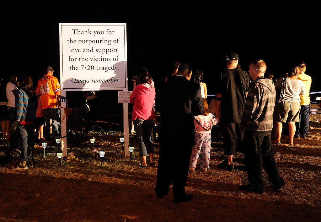 . AURORA, CO. - JULY 20: Hundreds of mourners marked the one year anniversary of the Aurora theater shootings Saturday morning, July 20, 2013.  They gathered on a hill across the street from the theater, lit candles in the moonlight, and remembered the dozen that died and the scores more that were injured a year ago.  Photo By Karl Gehring/The Denver Post