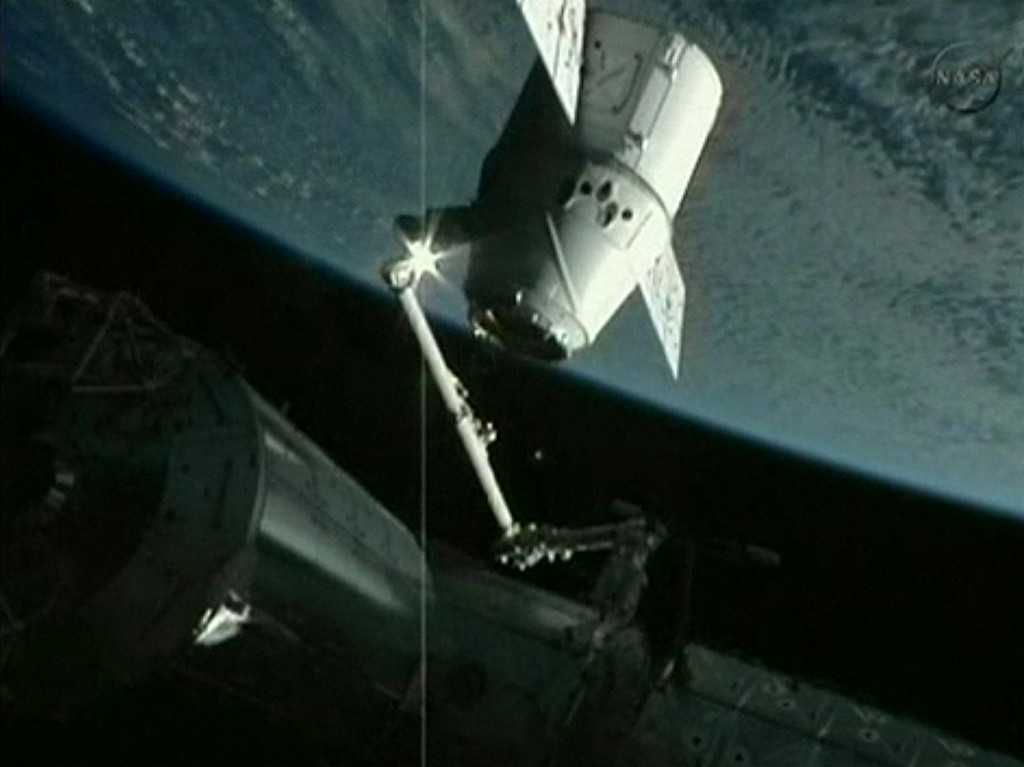 . In this frame grab from a NASA video, the robotic arm of the International Space Station holds the SpaceX Dragon capsule on May 25, 2012 as astronauts prepare to dock the capsule with the station. SpaceX has become the first private company to rendezvous with the orbiting lab. AFP PHOTO / NASA