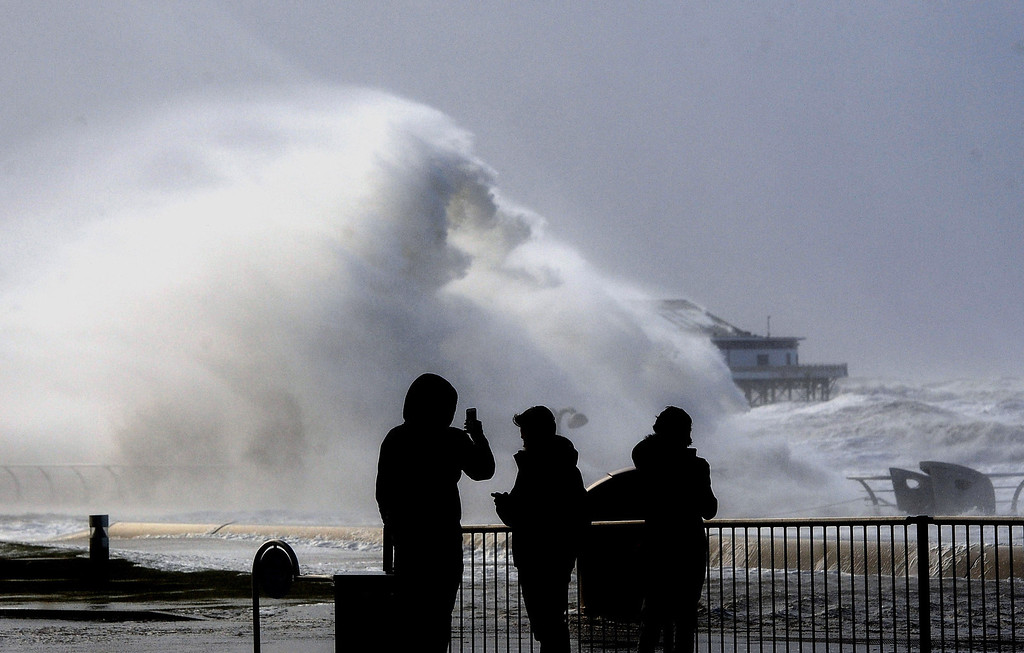 . People take photos on Blackpool\'s main promenade as severe gale force winds hit the area, in Blackpool, England, Thursday Dec. 5, 2013.  Much of northwestern Europe braced for a storm that was expected to bring flooding to coastal areas.  (AP Photo/PA, John Giles)