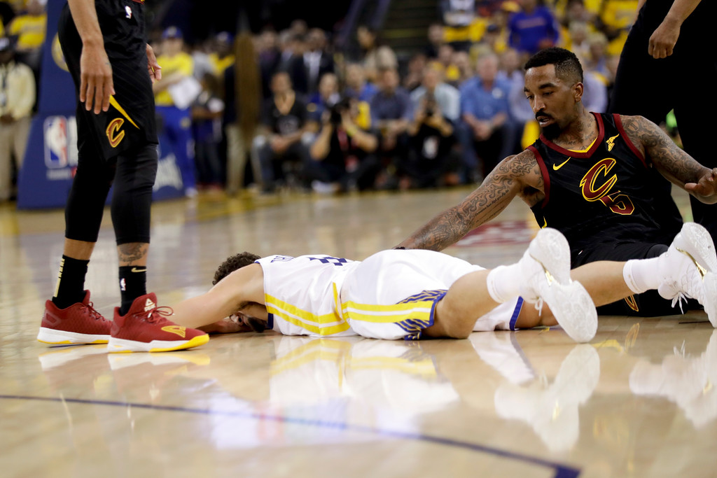. Golden State Warriors guard Klay Thompson, bottom, remains on the floor next to Cleveland Cavaliers guard J.R. Smith (5) during the first half of Game 1 of basketball\'s NBA Finals in Oakland, Calif., Thursday, May 31, 2018. (AP Photo/Marcio Jose Sanchez)