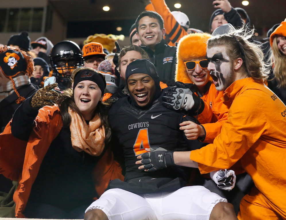 . Oklahoma State\'s Justin Gilbert (4) celebrates with fans following a victory oer Baylor in an NCAA college football game in Stillwater, Okla., Saturday, Nov. 23, 2013. Oklahoma State won 49-17. (AP Photo/Sue Ogrocki)