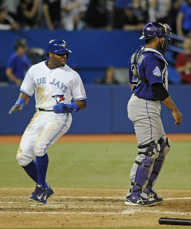. Rajai Davis #11 of the Toronto Blue Jays scores the game-winning run in the eighth inning as Wilin Rosario #20 of the Colorado Rockies looks on during inter-league MLB game action June 17, 2013 at Rogers Centre in Toronto, Ontario, Canada. (Photo by Brad White/Getty Images)