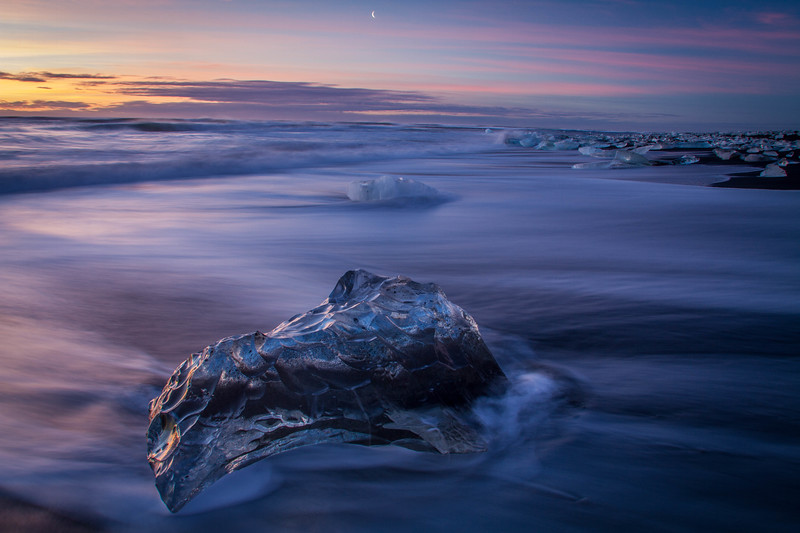 Sunset, moonrise, and icebergs on a black sand beach, Iceland