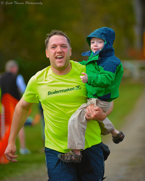 A father picks up his son for the last few meters of the Apple Run 15K Road Race in LaFayette, New York.