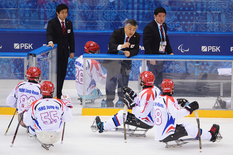 . Korea head coach Ik-Hwan Kim instructs his players during the Ice Sledge Hockey Preliminary Round Group A match between the Russia and Korea at Shayba Arena on March 8, 2014 in Sochi, Russia.  (Photo by Dennis Grombkowski/Getty Images)