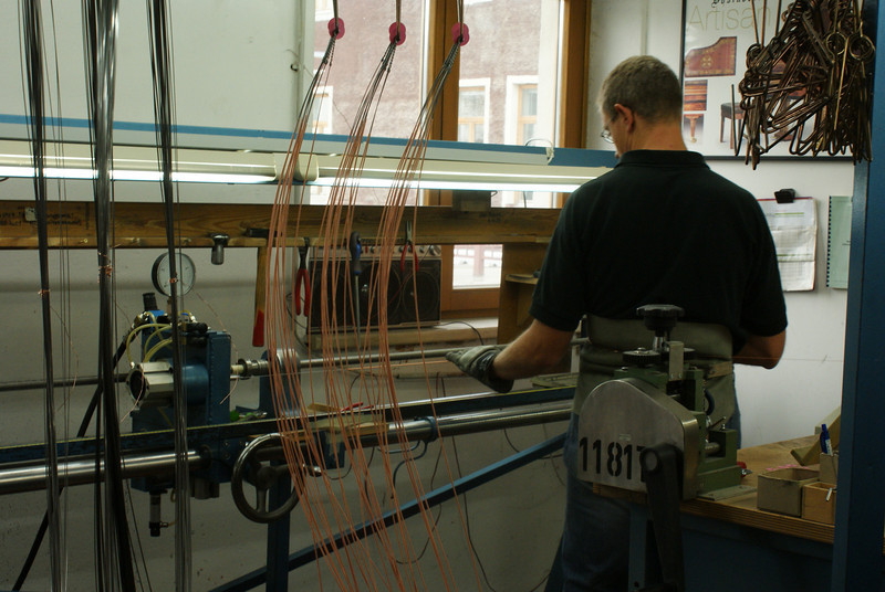 They are wrapping the base strings in copper coil to get the right sound.
