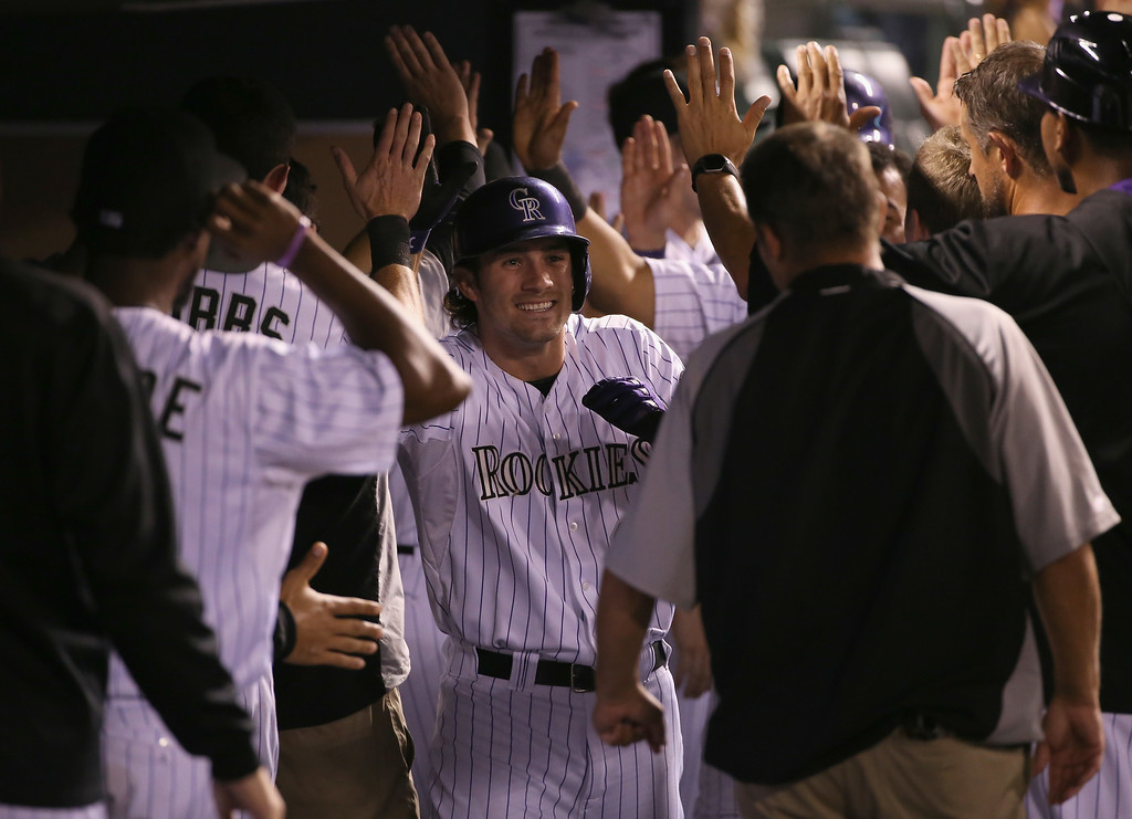 . DENVER, CO - AUGUST 14:  Charlie Culberson #23 of the Colorado Rockies celebrates his three run home run off of Alfredo Simon #31 of the Cincinnati Reds to give the Rockies a 7-2 lead in the fifth inning at Coors Field on August 14, 2014 in Denver, Colorado.  (Photo by Doug Pensinger/Getty Images)