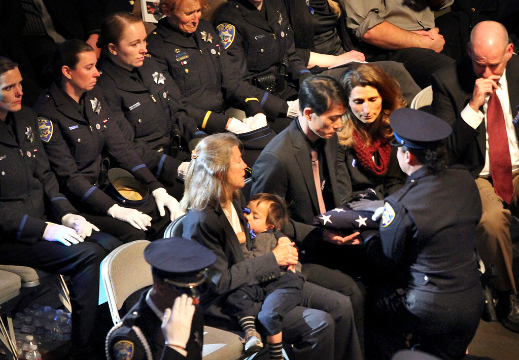 . Peter Wu is presented the American Flag by Santa Cruz police officer Laurel Schonfield at the memorial service for Wu�s partner, Santa Cruz police detective Elizabeth Butler and her colleague, Santa Cruz police detective Sgt. Loran �Butch� Baker� at HP Pavilion Thursday. Butler\'s older sister Alexis Butler sits beside him. (Shmuel Thaler/Sentinel)