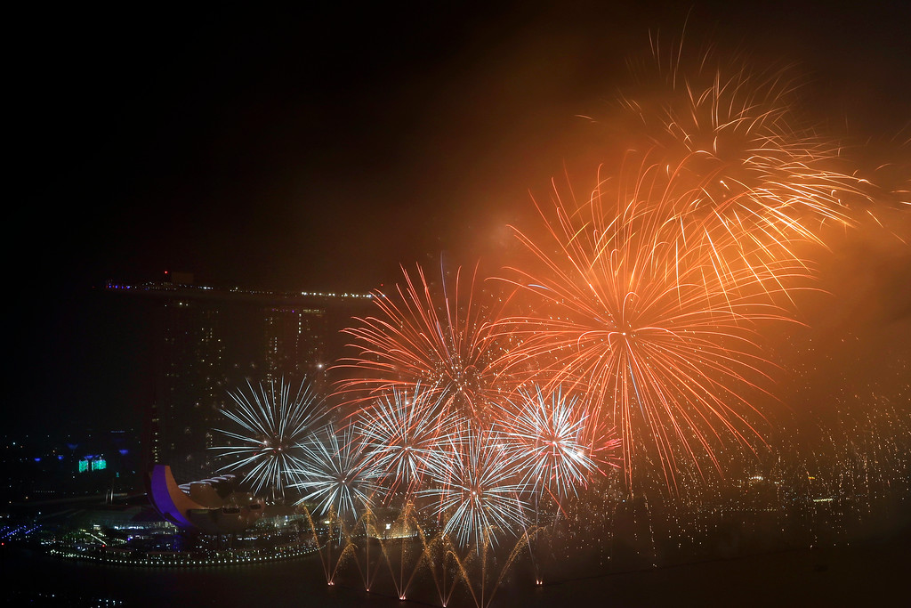 . Fireworks explode above Singapore\'s financial district at the stroke of midnight to mark the New Year\'s celebrations on Monday, Jan. 1, 2018, in Singapore. (AP Photo/Wong Maye-E)