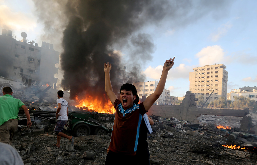 . In this Thursday, July 24, 2014, file photo, a Palestinian shouts in an area damaged in an Israeli airstrike in Gaza City in the Gaza Strip. On Thursday, July 31, 2014, the U.N.\'s top human rights official accused both Israel and Hamas of committing war crimes in the current Gaza fighting. (AP Photo/Hatem Moussa, File)