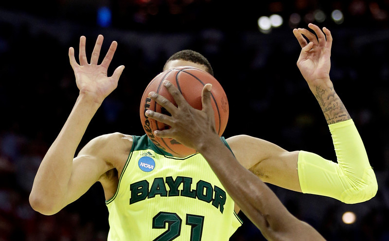. Baylor\'s Isaiah Austin (21) has his face covered by the ball as Nebraska\'s Leslee Smith\'s arm reaches for the ball during the second half of a second-round game in the NCAA college basketball tournament Friday, March 21, 2014, in San Antonio. Baylor won 74-60. (AP Photo/David J. Phillip)