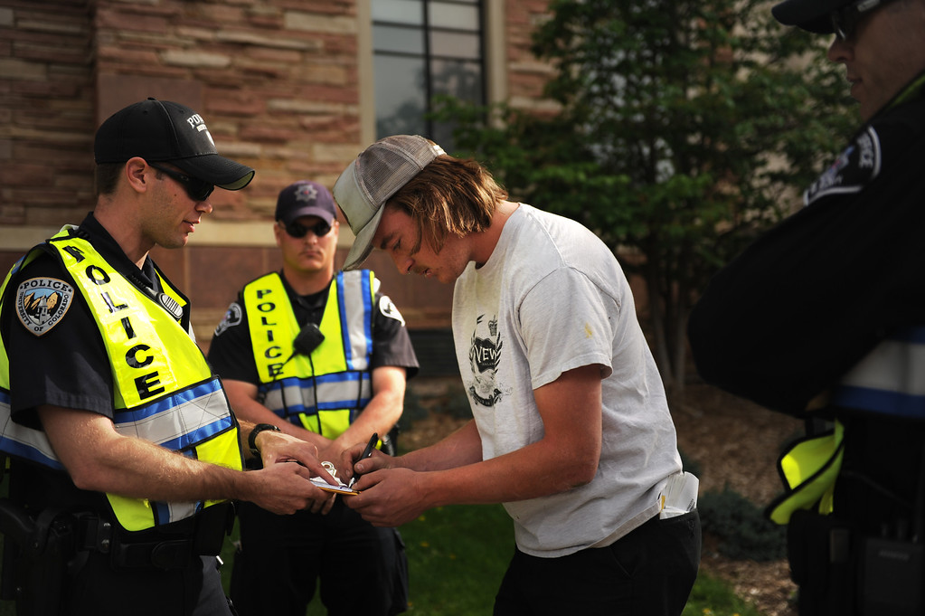 . 20 year old Nathan Ryan signs his ticket after making a break for the closed the Norlin Quad on Colorado University Boulder campus to crackdown on pro-marijuana protesters on 4-20 at the school in Boulder, Colorado, Friday, April 20, 2012.   Joe Amon, The Denver Post