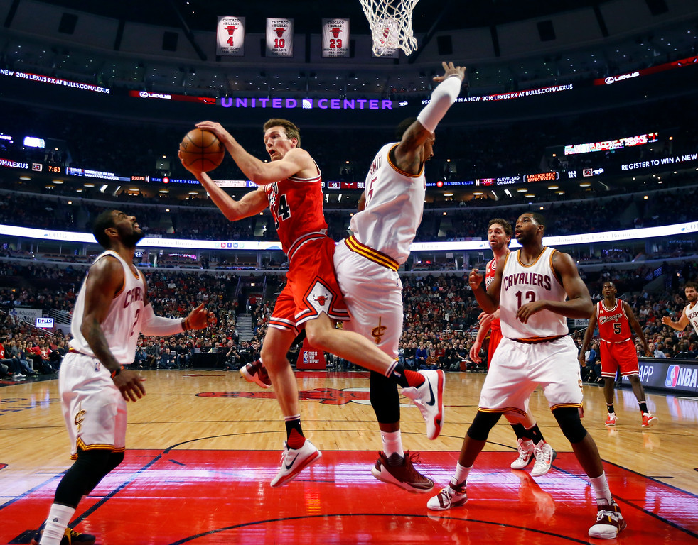 . Chicago Bulls guard Mike Dunleavy (34) grabs a rebound from Cleveland Cavaliers guard J.R. Smith (5) during the first half of an NBA basketball game in Chicago, on Friday, April 9, 2016.  (AP Photo/Jeff Haynes)