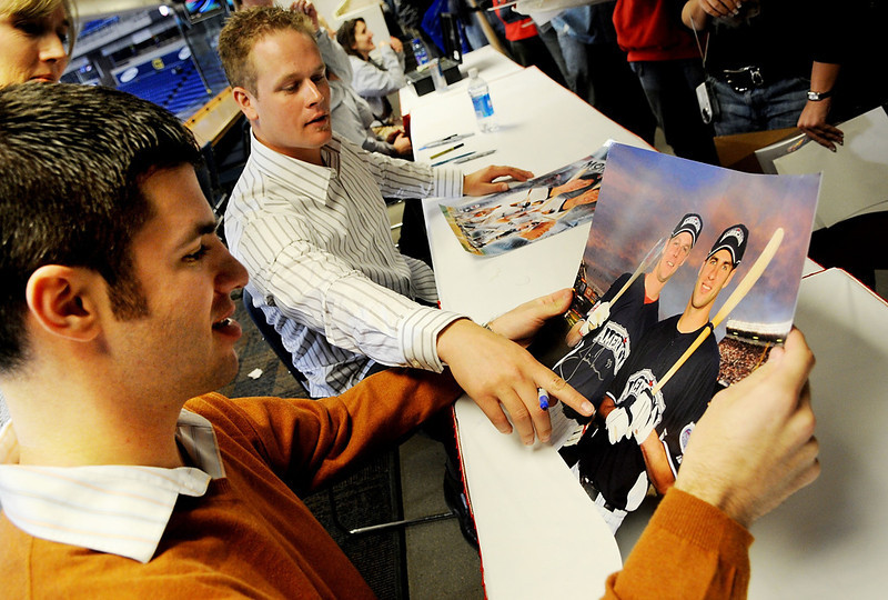 . The Twins\' Joe Mauer, left, and Justin Morneau, middle, discuss a photograph taken at the All-Star Game before signing it during an autograph session in the football press box during the kickoff of Twins Fest 2009 at the Metrodome on Friday night. (Pioneer Press: Sherri LaRose-Chiglo)