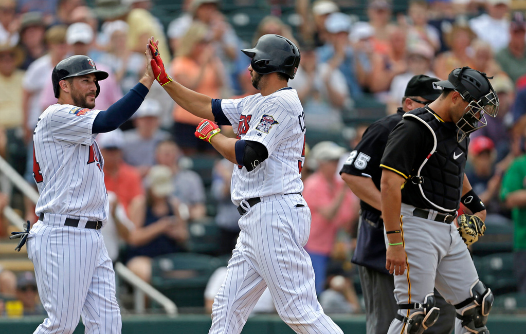 . Minnesota\'s Chris Colabello, right, is greeted at the plate by teammate Trevor Plouffe after the two scored on Colabello\'s two-run homer in the sixth inning against the Pirates. (AP Photo/Gerald Herbert)