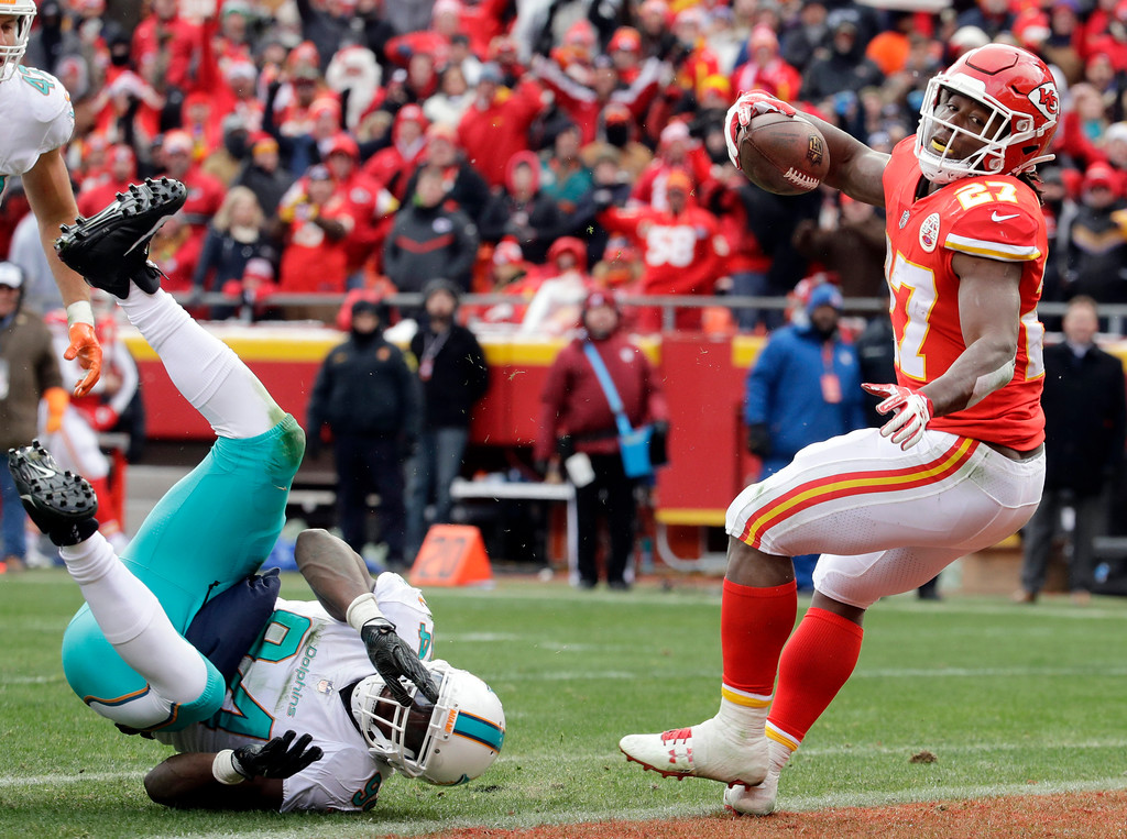 . Kansas City Chiefs running back Kareem Hunt (27) scores a touchdown away from Miami Dolphins linebacker Lawrence Timmons (94) during the first half of an NFL football game in Kansas City, Mo., Sunday, Dec. 24, 2017. (AP Photo/Charlie Riedel)