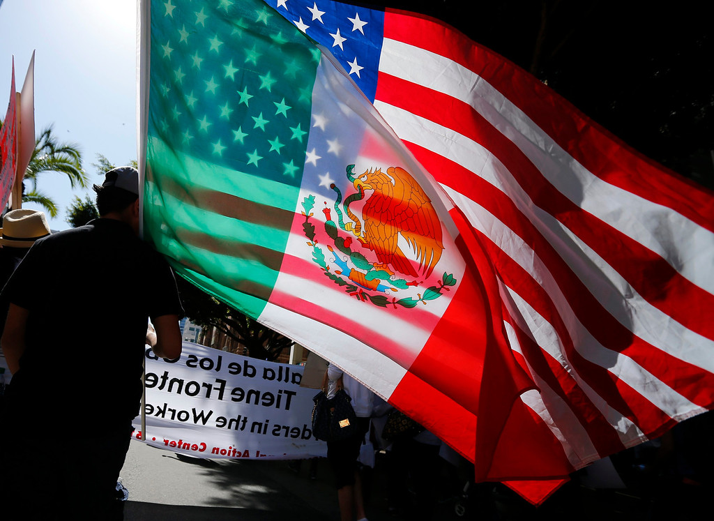 . A youth carries national flags of the U.S. and Mexico through the streets of San Diego, during a May Day demonstration and march in California May 1, 2013. Workers\' rights and immigration reform were supported in the demonstration.  REUTERS/Mike Blake