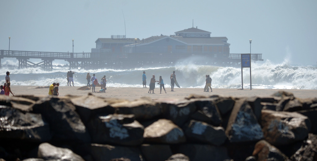 . People line the beach to watch the high waves pound the shore and pier in Seal Beach, CA on Wednesday, August 27, 2014. (Photo by Scott Varley, Daily Breeze)