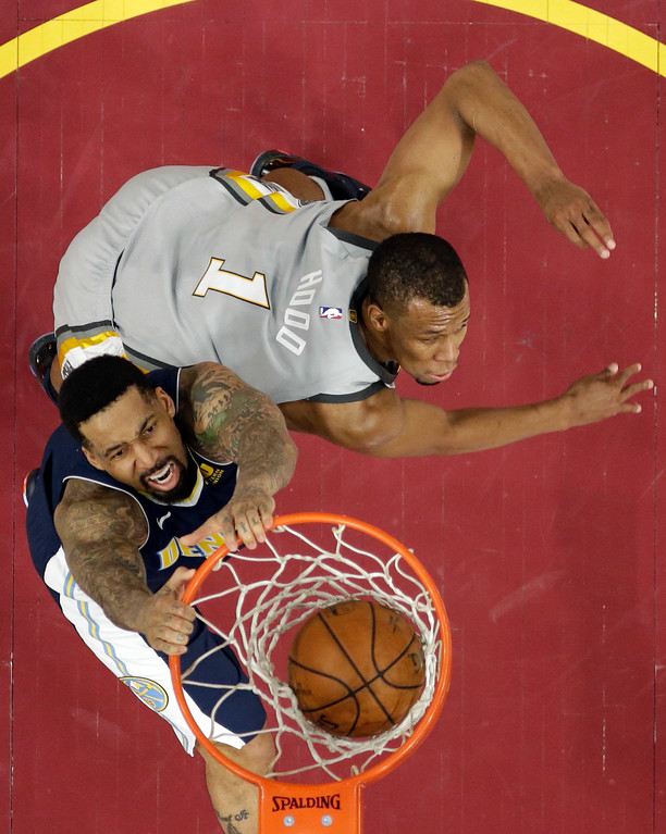 . Denver Nuggets\' Wilson Chandler, left, dunks the ball against Cleveland Cavaliers\' Rodney Hood in the second half of an NBA basketball game, Saturday, March 3, 2018, in Cleveland. The Nuggets won 126-117. (AP Photo/Tony Dejak)