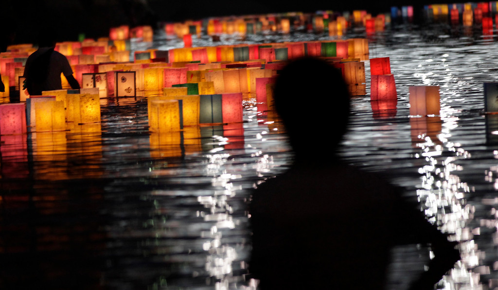 . A man watches paper lanterns for the repose of the souls of the atomic bombing victims in the Motoyasu River near the Atomic Bomb Dome in Hiroshima, western Japan, Tuesday, Aug. 6, 2013.  (AP Photo/Shizuo Kambayashi)