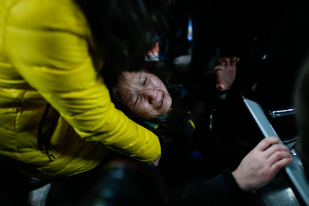 . A family member (C) cries on a bench at a hospital where some of the victims of a stampede by new year\'s revellers were sent in Shanghai on January 1, 2015. A stampede by New Year\'s revellers in Shanghai\'s historic riverfront area killed 35 people and injured dozens more, the city government said on January 1.   CHINA OUT   AFP PHOTOSTR/AFP/Getty Images