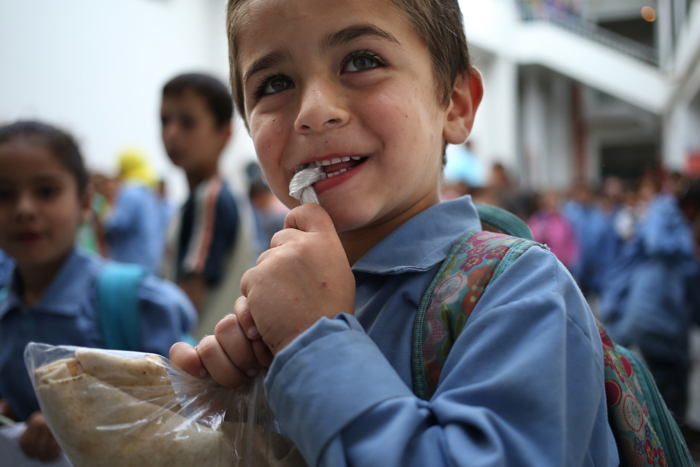 . In this picture taken on Thursday, May 29, 2014, a Syrian refugee student open his plastic food bag during a recess at a Lebanese public school where only Syrian students attend classes in the afternoon, in Kaitaa village in north Lebanon. (AP Photo/Hussein Malla)