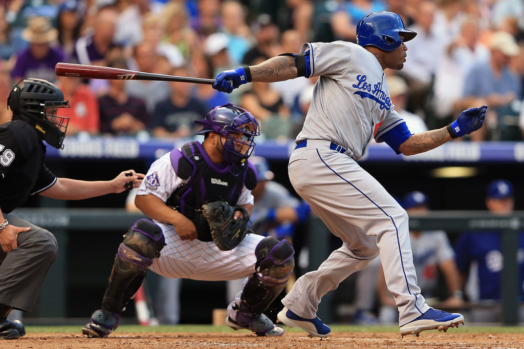 . Carl Crawford #25 of the Los Angeles Dodgers hits a two RBI single off of starting pitcher Jhoulys Chacin #45 of the Colorado Rockies as catcher Wilin Rosario #20 of the Colorado Rockies backs up the plate to give the Dodgers a 3-0 lead in the second inning at Coors Field on September 3, 2013 in Denver, Colorado.  (Photo by Doug Pensinger/Getty Images)