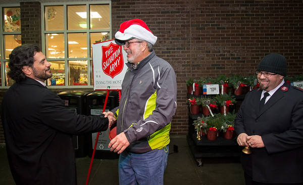 12/09/19 Wesley Bunnell | StaffrrState Senator Gennaro Bizzarro, L, and State Rep. William Petit Jr. , R, shake hands as they meet outside of the Corbin Ave Stop & Shop on Monday evening to help collect for the Salvation Army. Lt. Willie Rodriguez of the New Britain Salvation Army looks on.