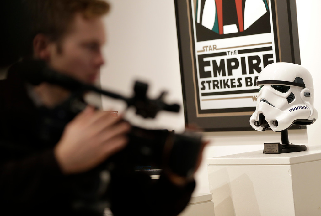 . A camera man takes pictures of toys and other memorabilia from the \'Star Wars\' movie series on display during a press preview at Sotheby\'s in New York, Wednesday, Dec. 2, 2015. Sotheby\'s is holding an online auction of hundreds of rare and original objects associated with the space odyssey series. (AP Photo/Seth Wenig)
