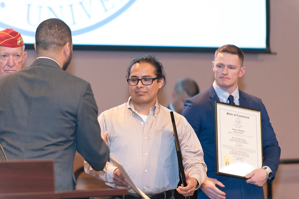 11/12/18 Wesley Bunnell | Staff CCSU held a Veterans Day Observance on Monday afternoon in Alumni Hall which featured honoring three local veterans. Honoree Mike Curiel, receives a proclamation from the City of New Britain which was read by New Britain Alderman Kristian Rosado.