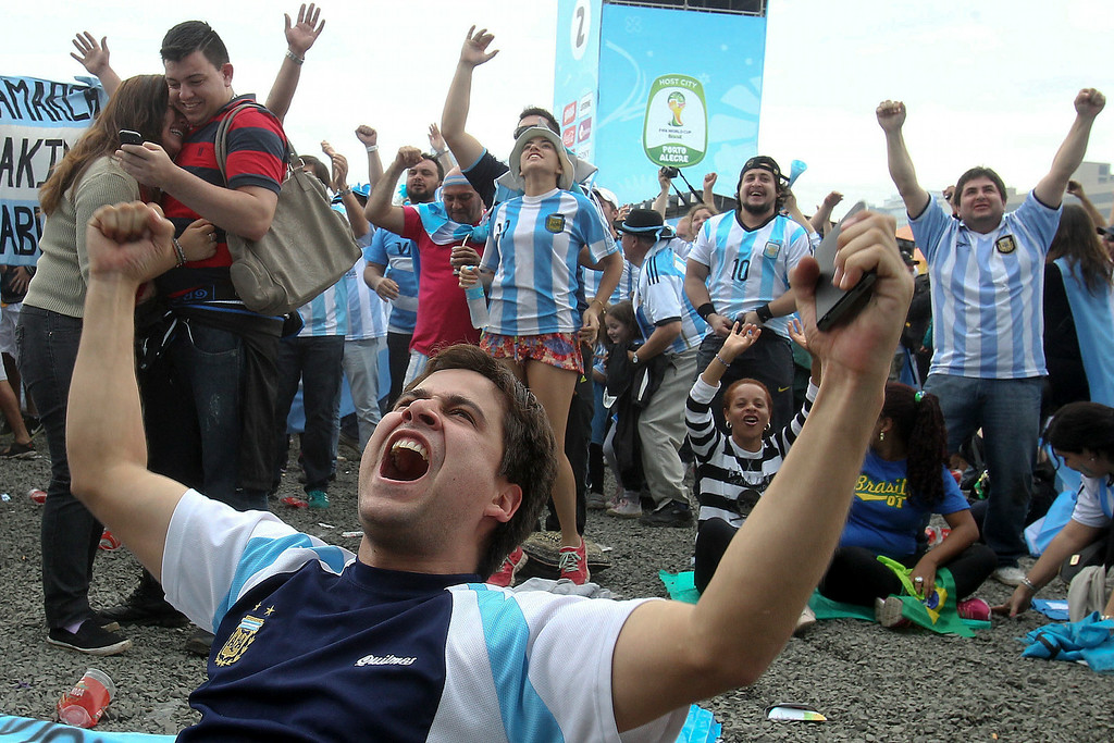 . Argentina soccer fans celebrate after watching their side score a goal, via a live telecast of the World Cup group F match between Argentina and Nigeria, inside the FIFA Fan Fest area, in Porto Alegre, Brazil, Wednesday, June 25, 2014. (AP Photo/Nabor Goulart)