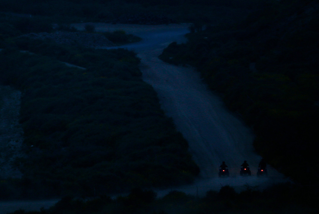 . U.S. Customs and Border Patrol agents patrol on their ATVs at night along the international border between Mexico and the United States near San Diego, California, March 26, 2013. Picture taken March 26, 2013. REUTERS/Mike Blake
