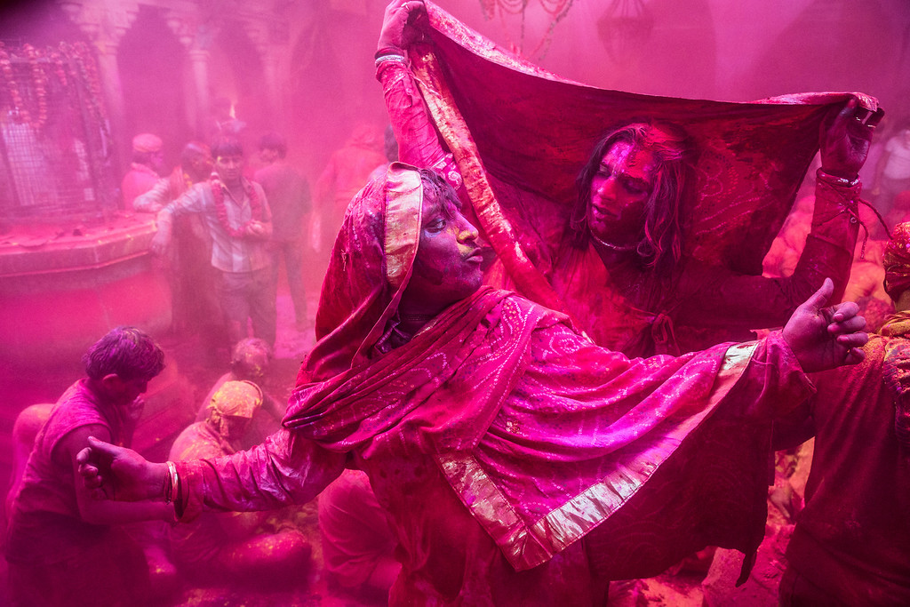 . Transgender Hindu devotees dance as others  play with color during Lathmaar Holi celebrations on March 21, 2013 in the village of Barsana, near Mathura, India. The tradition of playing with colours on Holi draws its roots from a legend of Radha and the Hindu God Krishna. It is believed that young Krishna was jealous of Radha\'s fair complexion since he himself was himself very dark. After questioning his mother Yashoda on the darkness of his complexion, Yashoda, teasingly asked him to colour Radha\'s face in which ever colour he wanted. In a mischievous mood, Krishna applied colour on Radha\'s face. The tradition of applying color on one\'s beloved is being religiously followed till date. (Photo by Daniel Berehulak/Getty Images)