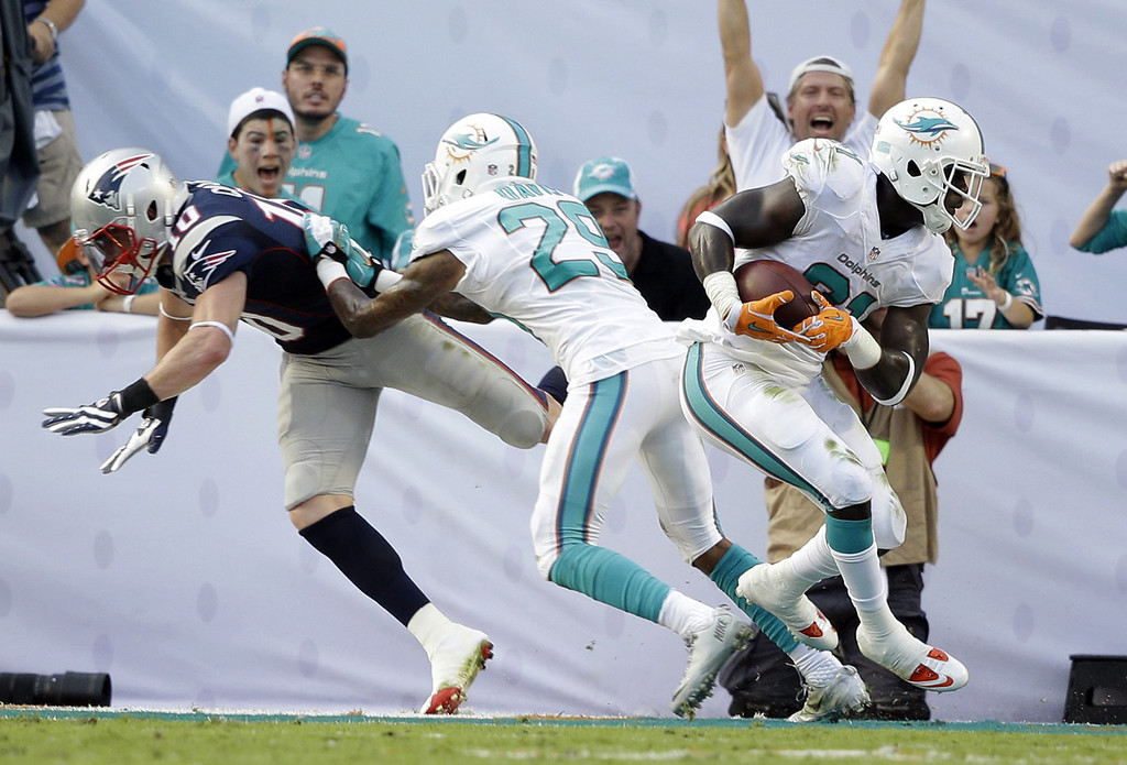 . Miami Dolphins Michael Thomas (31) intercepts a ball intended for New England Patriots wide receiver Austin Collie (10) as Dolphins cornerback Will Davis (29) defends during the second half of an NFL football game on Sunday, Dec. 15, 2013, in Miami Gardens, Fla. The Dolphins defeated the Patriots 24-20. (AP Photo/Lynne Sladky)
