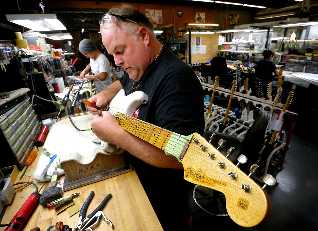 . A finished Fender Stratocaster is adjusted by Kenneth Maas in the Fender Custom Shop in Corona, Calif. on Tuesday, Oct. 15, 2013. Leo Fender developed the instrument in a small workshop in Fullerton, Calif. six decades ago. (AP Photo/Matt York)