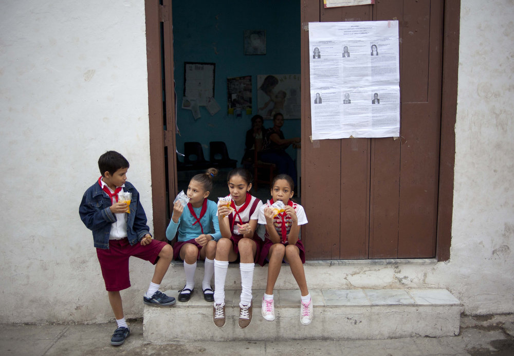 Description of . Cuban schoolchildren, who check voters properly cast their ballots, take a break at a polling station during parliament elections in Havana, Cuba, Sunday, Feb. 3, 2013. More than 8 million islanders are eligible to vote and will approve 612 members of the National Assembly and over 1,600 provincial delegates. (AP Photo/Ramon Espinosa)
