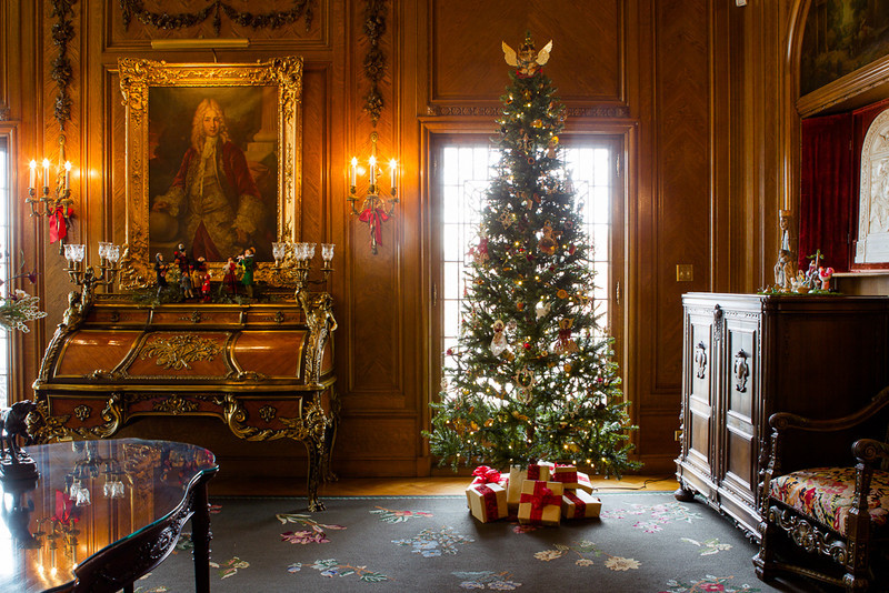 . Antique furnishings in a room of the Governor\'s mansion are aglow from decorated sconces and tree lights. Photo by Mark Broste