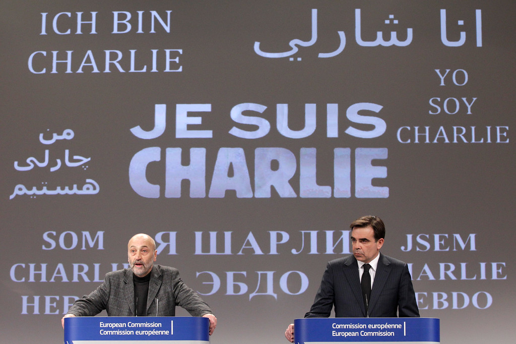 ". The Brussels International Press Association President Tom Weingaertner, left, and European Commission Chief Spokesperson Margaritis Schinas address the media in front of a banner that reads: ""Je suis Charlie (I Am Charlie)\"", as they pay respect for the victims of Wednesday\'s terror attack in Paris, at the European Commission headquarters, in Brussels, Thursday, Jan. 8, 2015. Eight journalists, two police officers, a maintenance worker and a visitor were killed, and eleven people wounded in a terrorist attack against French satirical newspaper Charlie Hebdo in Paris. (AP Photo/Yves Logghe)"