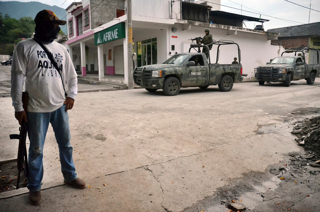 . Mexican army vehicles drive past an armed member of a local self-defense group wearing  a white T-shirt with the slogan \'For a Free Aquila\' in the town of Aquila, Mexico, early Wednesday, July 24, 2013. Mexico\'s rough western state of Michoacan, where Aquila is located, is proving just as tough a thorn in the side of President Enrique Pena Nieto as it was for his predecessor after gunmen believed to be working for the Knights Templar cartel launched a coordinated series of a half-dozen ambushes on federal police convoys last Tuesday followed by yet another self-defense group that has sprung up to fight against the Knights Templar. (AP Photo/Gustavo Aguado)