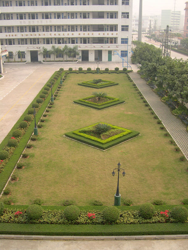 Beautifully manicured factory garden with dormitory in the background