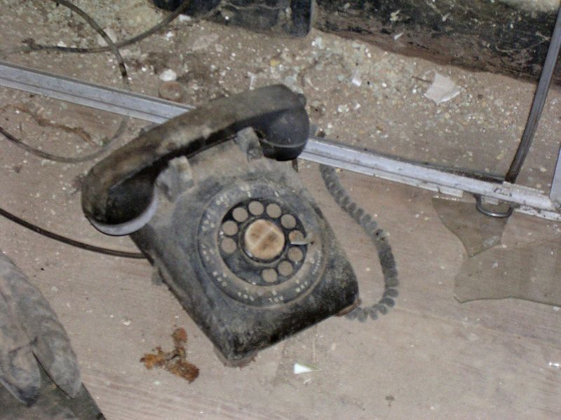 An old rotary dial phone sits on the floor of the tackroom. As she aged, Nancy Smith became a recluse, and probably used this phone until the end of her life in 1996.