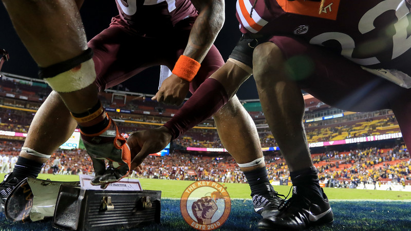 The Hokies grab some FedEx field grass to place into the lunchpail to bring back to Blacksburg. (Mark Umansky/TheKeyPlay.com)